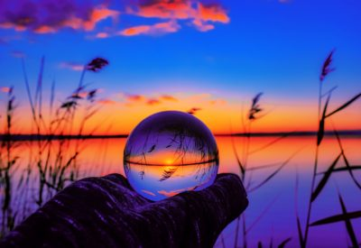 A beautiful selective focus shot of a crystal ball reflecting the breathtaking sunset with unique colors