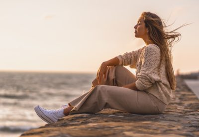 A shallow focus shot of a young blonde Caucasian woman in a wool cardigan during a beautiful sunset at the beach by the sea