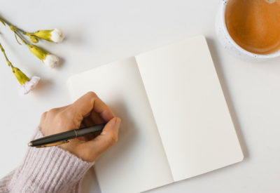 woman-writing-with-pen-on-blank-page-against-white-background