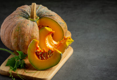 chopped raw pumpkin put on wooden cutting board